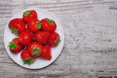 Heap of strawberries in bowl on old wooden background. Top view. Heap of fresh strawberries in bowl on old wooden background. Top view stock photography