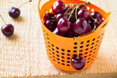 Heap of sweet cherries in basket. Heap of sweet cherries in orange basket on wooden background Stock Images