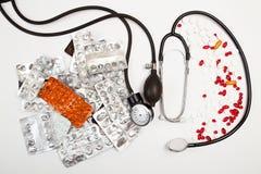 Heap of tablets, pills, empty blisters, tonometer, phonendoscope Royalty Free Stock Image