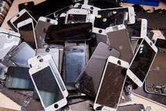 A heap of the top covers with displays of broken mobile phones. In the mobile service office stock photography