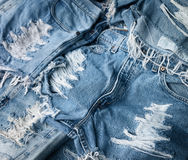 Heap of torn and frayed, threadbare jeans. Denim shorts Stock Photography