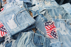 Heap of torn and frayed, threadbare jeans. Denim shorts with bright pockets with flag elements Royalty Free Stock Photo