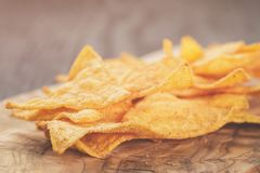 Heap of tortilla chips on olive board on wooden table Stock Photo