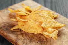 Heap of tortilla chips on olive board on wooden Royalty Free Stock Images