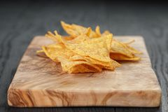 Heap of tortilla chips on olive board on wooden Stock Photo