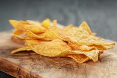 Heap of tortilla chips on olive board on wooden Royalty Free Stock Photography