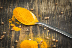 Heap of turmeric on a metal spoon Stock Images