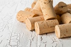 Heap of unused, new, brown natural wine corks on white wooden bo Royalty Free Stock Photography