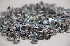 Heap of various bolts, nuts, screws and washers lying in a heap, front view on gray background royalty free stock photo