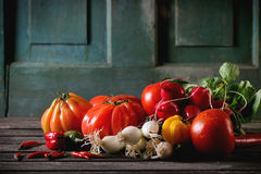 Heap of vegetables. Heap of fresh ripe colorful vegetables tomatoes, chili peppers, green onion and bunch of radish over old wooden table. Dark rustic atmosphere Stock Photography