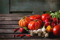 Heap of vegetables. Heap of fresh ripe colorful vegetables tomatoes, chili peppers, green onion and bunch of radish over old wooden table. Dark rustic atmosphere Royalty Free Stock Images