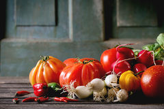 Heap of vegetables. Heap of fresh ripe colorful vegetables tomatoes, chili peppers, green onion and bunch of radish over old wooden table. Dark rustic atmosphere Stock Images
