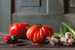 Heap of vegetables. Heap of fresh ripe colorful vegetables tomatoes, chili peppers, green onion and bunch of radish over old wooden table. Dark rustic atmosphere Stock Image
