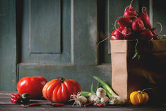 Heap of vegetables. Heap of fresh ripe colorful vegetables tomatoes, chili peppers, green onion and bunch of radish in paper bag over old wooden table. Dark Royalty Free Stock Images