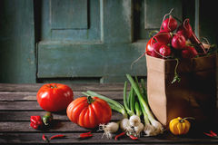 Heap of vegetables. Heap of fresh ripe colorful vegetables tomatoes, chili peppers, green onion and bunch of radish in paper bag over old wooden table. Dark Stock Photos