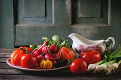 Heap of vegetables. Heap of fresh ripe colorful vegetables tomatoes, chili peppers, green onion and bunch of radish on vintage plate and porcelain gravy boat Stock Image
