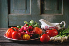 Heap of vegetables. Heap of fresh ripe colorful vegetables tomatoes, chili peppers, green onion and bunch of radish on vintage plate and porcelain gravy boat Royalty Free Stock Photography