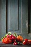 Heap of vegetables. Heap of fresh ripe colorful vegetables tomatoes, chili peppers, green onion and bunch of radishover old wooden table. Dark rustic atmosphere Stock Photography