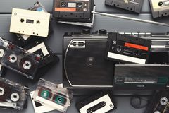 Heap of vintage audio cassettes and tape recorder at gray background Stock Photography