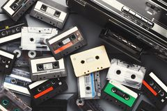 Heap of vintage audio cassettes and tape recorder at gray background Royalty Free Stock Photo
