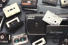 Heap of vintage audio cassettes and tape recorder at gray background Stock Images