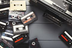 Heap of vintage audio cassettes and tape recorder at gray background Stock Photos