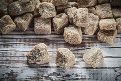 Heap of vintage cane sugar cubes on wooden board Royalty Free Stock Image