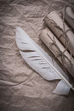 Heap of vintage paper rolls feather on crumpled wrapping sheet Stock Photography