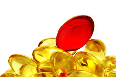 Heap of the vitamin capsules. Red vitamin dragee on a heap of gelatinous capsules Royalty Free Stock Photo