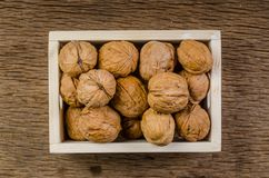 Heap of walnuts in wooden crate. Walnuts in wooden crate on table stock images