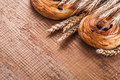 Heap of wheat ears sweet raisin pastry on oaken. Wooden board food and drink concept Royalty Free Stock Image
