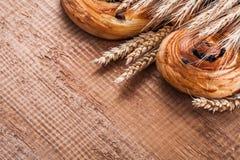 Heap of wheat ears sweet raisin pastry on oaken Royalty Free Stock Image