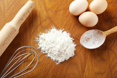 Heap of wheat flour with eggs, rolling pin and spikelets on brow Royalty Free Stock Photography