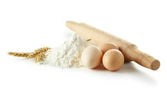 Heap of wheat flour with eggs, rolling pin and spikelets isolate Royalty Free Stock Photography