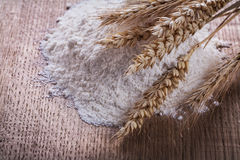 Heap white flour with ears of wheat rye on wooden Stock Images