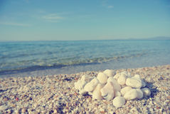 Heap of white pebbles on pebbly beach; faded, retro style. Heap of white pebbles on pebbly beach, on a sunny day, with blue sea in the background. Image filtered Stock Photo