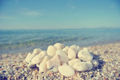 Heap of white pebbles on pebbly beach; faded, retro style Royalty Free Stock Image