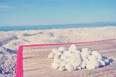 Heap of white pebbles on white sandy beach; faded, retro style Stock Image