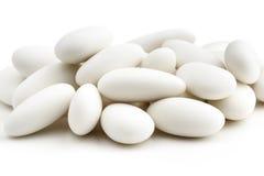Heap of white sugared almonds. On white background stock photo