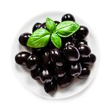 Heap of Whole black olives with basil leaf on a plate  isolated. On white background. Glossy  Olive canned  fruit.  Ingredients for cooking. Top view Stock Image