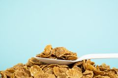 Heap of whole grain cereals in blue background. Healthy breakfast concept: close-up image of spoon full of muesli royalty free stock photo