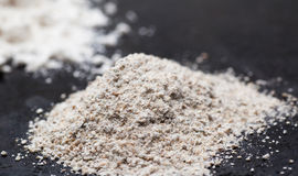 Heap of whole grain flour on the black. Selective focus, macro Stock Image