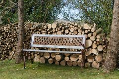 Heap of wood logs and bench in a garden. Heap of wood logs and bench made in wrought iron and wood in a garden during winter stock images