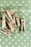 Heap of wooden clothespins on green textile Royalty Free Stock Photography