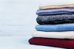 Heap of wool sweaters and knitted winter clothes on blue wooden background. Copy space for text. Stock Photography