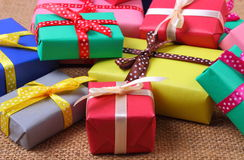 Heap of wrapped gifts for Christmas or other celebration on jute canvas Stock Image
