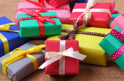 Heap of wrapped gifts for Christmas or other celebration on jute canvas Stock Photos