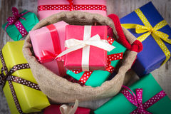 Heap of wrapped gifts for Christmas or other celebration on old wooden plank Stock Photography