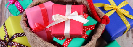 Heap of wrapped gifts for Christmas or other celebration on old wooden plank Royalty Free Stock Image