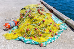 Heap of yellow fishnet on ground at sea Royalty Free Stock Photo